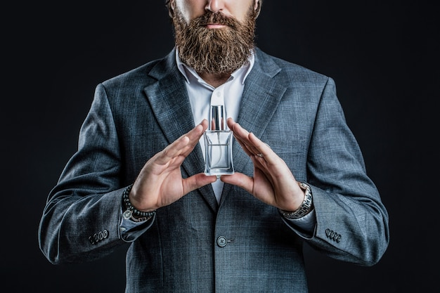 Maschio tenendo in mano una bottiglia di profumo.