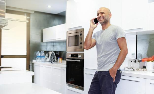 Capofamiglia maschio parlando al telefono nella cucina di casa sua.copyspace