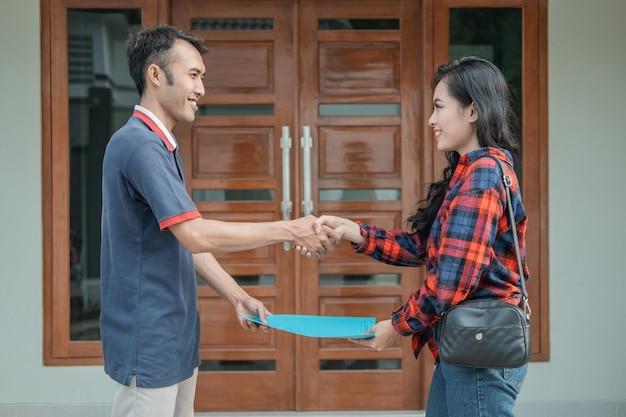 Imprenditore edile maschio consegna certificato di casa al cliente mentre stringe la mano con la nuova casa