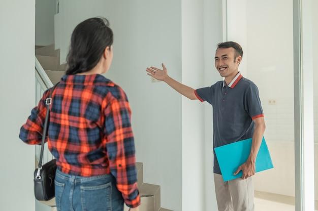 Imprenditore edile maschio con un gesto della mano invita i clienti a salire le scale per esplorare le stanze della casa