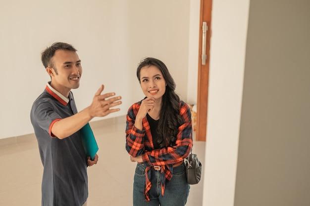 Gli imprenditori edili di sesso maschile mostrano le stanze a clienti femminili mentre esplorano all'interno di una nuova casa