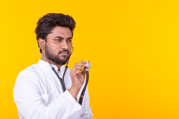 Medico indiano maschio che tiene uno stetoscopio nelle sue mani per ascoltare un paziente in posa su una parete gialla. concetto di trattamento e recupero. copyspace.