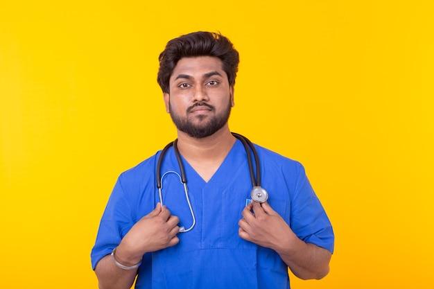 Medico indiano maschio con uno stetoscopio in posa su una parete gialla. concetto di trattamento e recupero. copyspace.