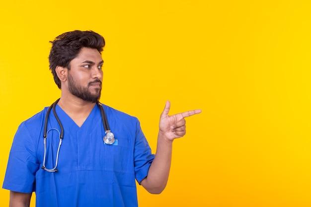 Medico indiano maschio con uno stetoscopio in posa su una parete gialla che punta su copyspace. concetto di trattamento e recupero.