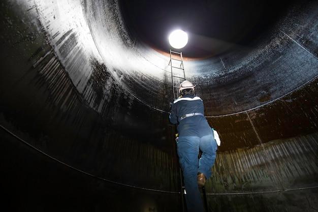 Il maschio all'interno sale l'ispezione visiva del serbatoio dell'olio combustibile pesante di stoccaggio delle scale nello spazio ristretto