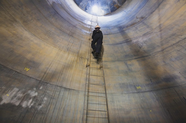 Il maschio all'interno sale il serbatoio di ispezione visiva di stoccaggio delle scale nello spazio confinato