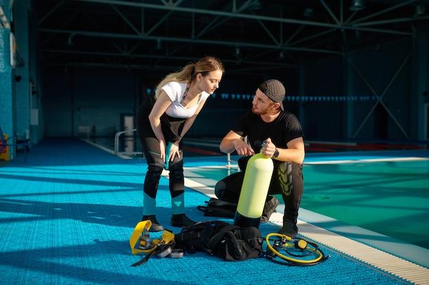 Istruttore maschio spiega come funziona l'attrezzatura subacquea