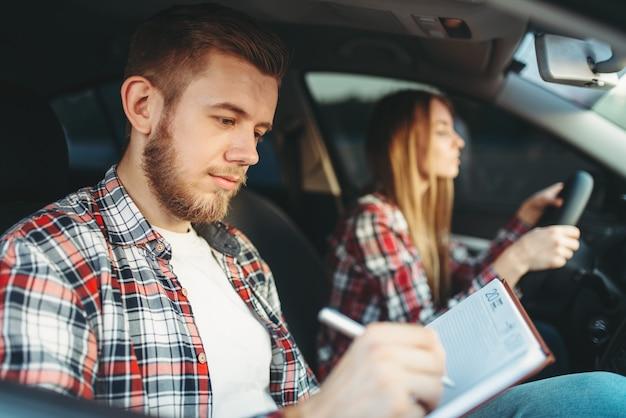 Istruttore maschio e studentessa, lezione di guida