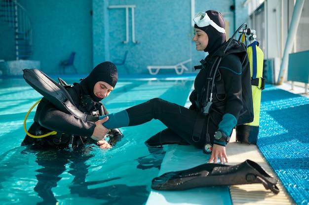 Istruttore maschio aiuta la donna a indossare le pinne, immersioni
