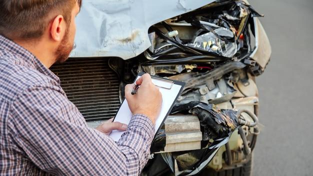 Agente assicurativo maschio con assicurazione auto vuota contro l'auto distrutta in un incidente stradale su strada. fanale anteriore auto rotto fracassato sull'incidente d'auto. assicurazione sanitaria sulla vita auto. banner web.