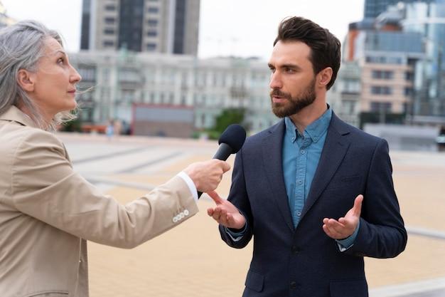 Uomo intervistato da giornalisti all'aperto
