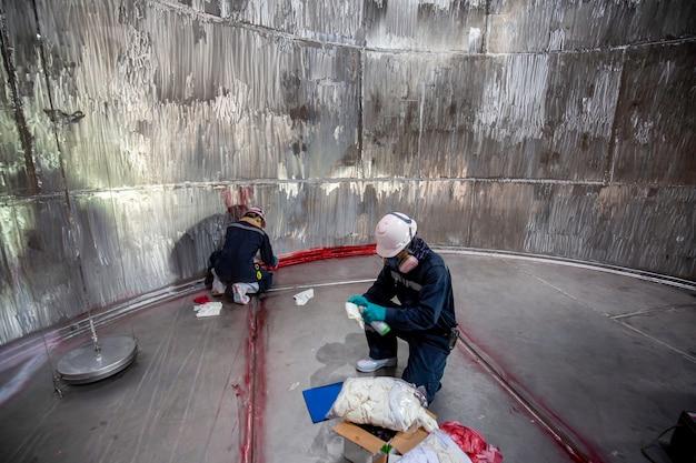 Maschio nell'ispezione del lavoro colore chimico vernice rossa liquido penetrante e ispezione per la pulizia della saldatura inossidabile rosso con l'area spazio confinato