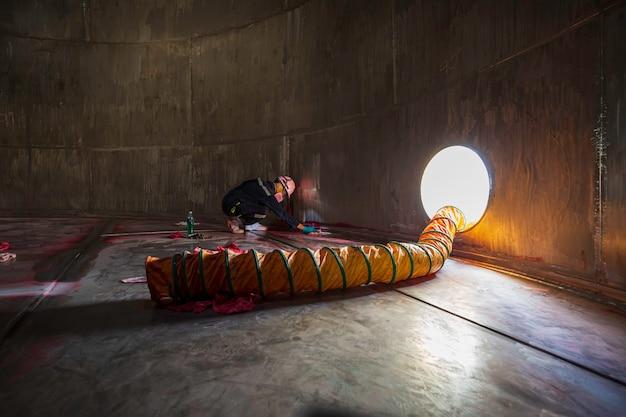 Maschio nel processo di ispezione del lavoro colore chimico vernice saldatura pulizia rosso al con ventilatore in acciaio inox aria fresca nello spazio limitato del serbatoio di stoccaggio dell'olio