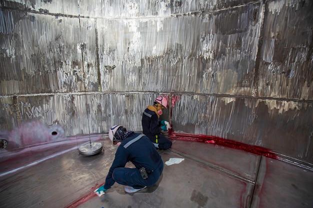 Maschio nel processo di ispezione del lavoro colore chimico vernice saldatura pulizia rosso con serbatoi in acciaio inossidabile l'area spazio confinato