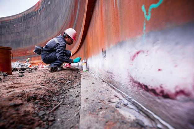 Maschio nel processo di ispezione del lavoro colore chimico vernice saldatura pulizia sviluppatore bianco con serbatoi in acciaio al carbonio l'area spazio confinato