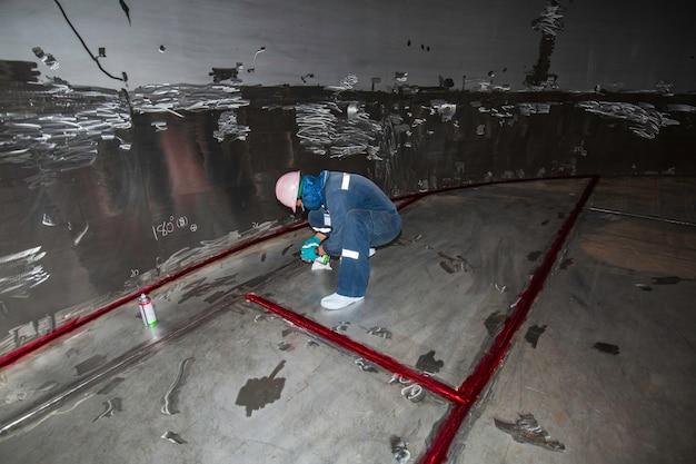 Maschio nel processo di ispezione del lavoro vernice di colore chimico saldata in rosso con serbatoi di acciaio inossidabile nell'area confinata