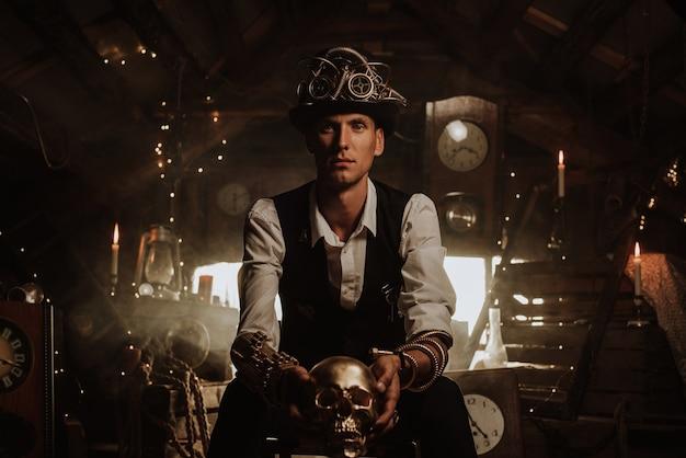 Inventore maschio in un vestito steampunk con un cappello, un cilindro con occhiali e meccanismi