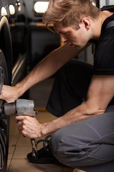 Il maschio sta riparando da solo la ruota dell'auto, utilizzando strumenti speciali per la riparazione