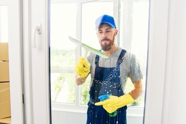 Bidello maschio utilizzando un tergipavimento per pulire una finestra in un ufficio indossando un grembiule e guanti mentre lavora