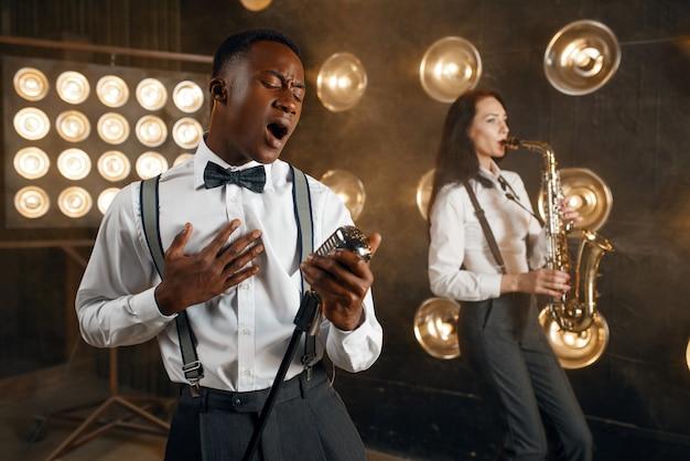 Jazzman maschio e sassofonista femmina con sassofono sul palco con faretti. artisti jazz che suonano sulla scena