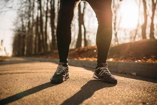 Pareggiatore maschio gambe, allenamento mattutino all'aperto. corridore in abbigliamento sportivo in allenamento nel parco
