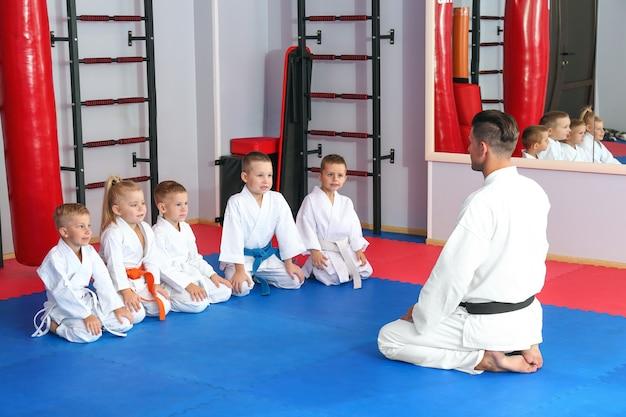 Istruttore di karate maschio con bambini piccoli nel dojo