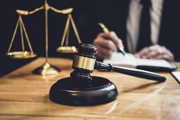 Avvocato o giudice maschio che lavora con le carte del contratto, i libri di legge e il martelletto di legno sul tavolo nell'aula di tribunale