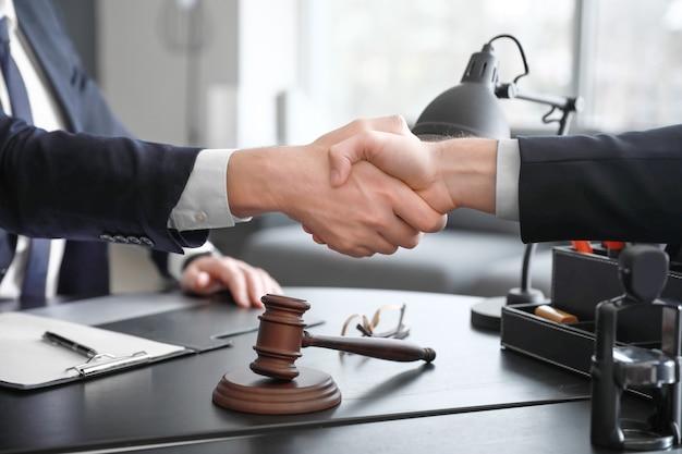 Avvocato maschio con il cliente che agitano le mani in ufficio