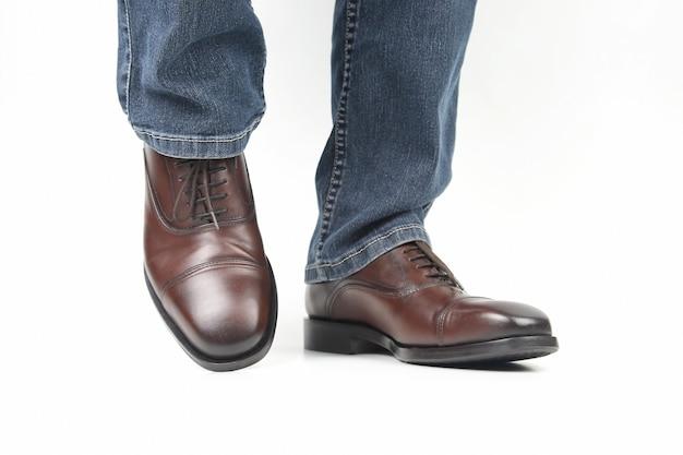 Piedini maschii in jeans e scarpe classiche marroni su priorità bassa bianca