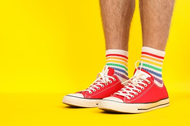 Piedini maschii in scarpe da ginnastica rosse e calzini lgbt su giallo