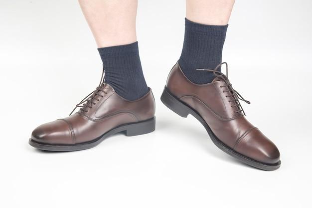 Piedini maschii in calzini e scarpe classiche marroni su sfondo bianco