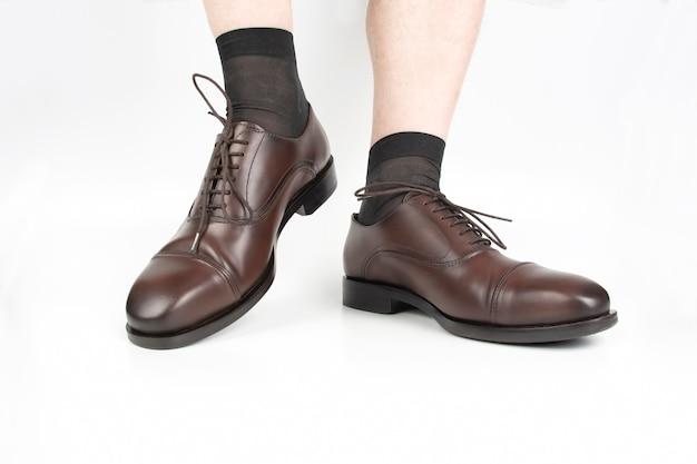 Piedini maschii in calzini e scarpe classiche marroni su bianco