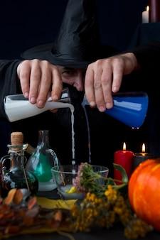 Un alchimista mago maschio prepara una pozione vacanze di halloween