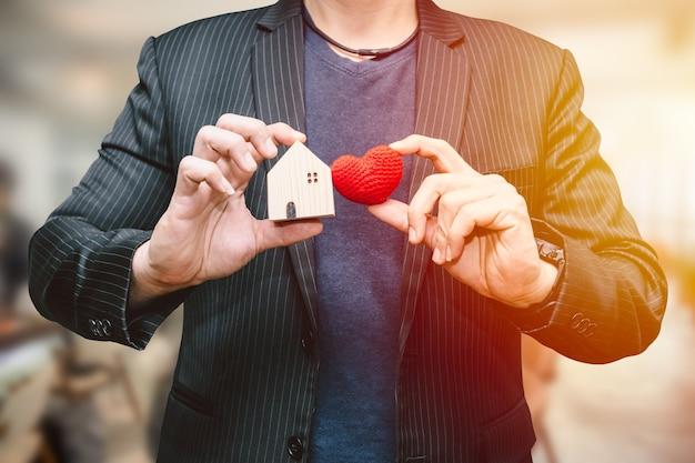 Mano dell'uomo maschio che tiene la piccola casa e il segno del cuore per il concetto di servizio di alloggio per la casa d'amore o per affari