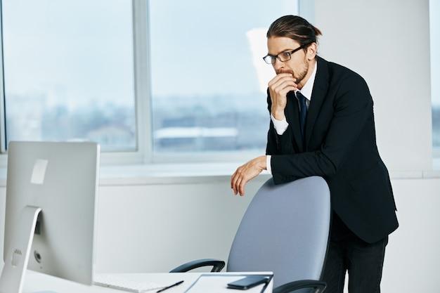 Manager maschio vicino alle tecnologie del computer desktop dell'ufficio