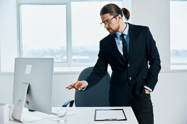 Il manager maschio nei gesti dell'ufficio con il suo computer delle mani