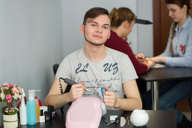 Manicure maschio seduto a un tavolo nel salone e ottenere una manicure