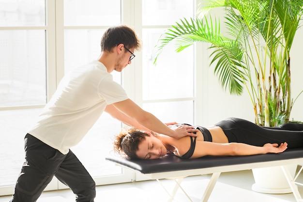 Massaggiatore maschio che esegue osteopatia di valutazione toracica