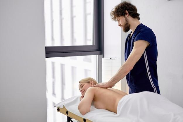 Massaggiatore maschio che massaggia la schiena e le scapole della donna sdraiata sul lettino da massaggio al salone spa. bella giovane donna bionda con una pelle perfetta che riceve un massaggio rilassante da un professionista
