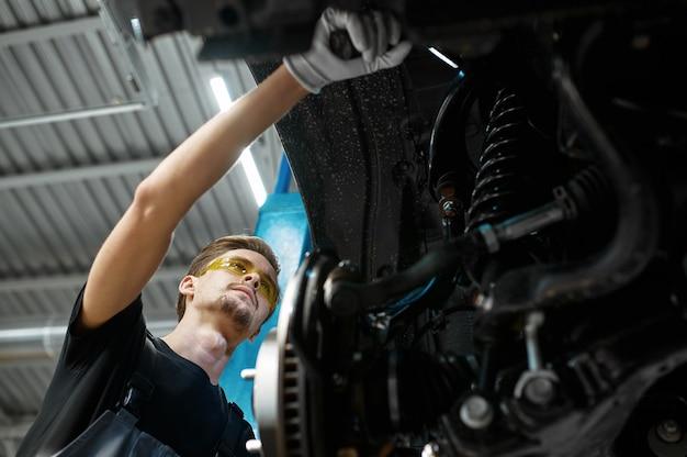 Il meccanico maschio controlla le sospensioni dell'auto, il servizio auto