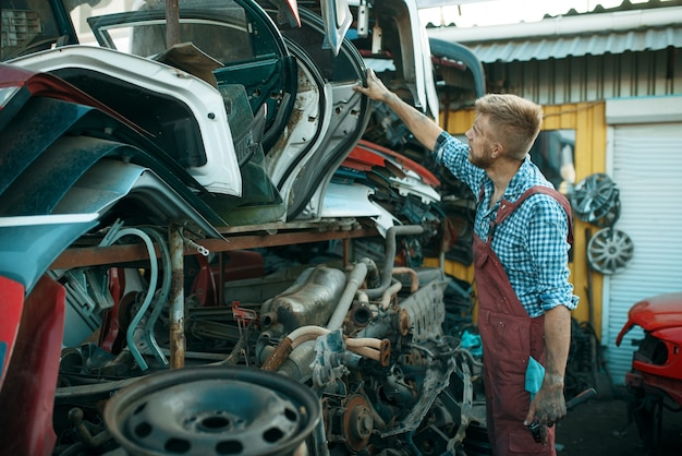 Meccanico maschio che sceglie la porta sulla discarica di auto. rottami di automobili, cianfrusaglie di veicoli, rifiuti di automobili. trasporti abbandonati, danneggiati e frantumati, cantiere di demolizione