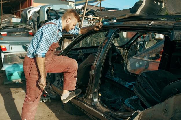 Il meccanico maschio smonta l'auto sulla discarica. rottami di automobili, cianfrusaglie di veicoli, rifiuti di automobili. trasporti abbandonati, danneggiati e frantumati, cantiere di demolizione