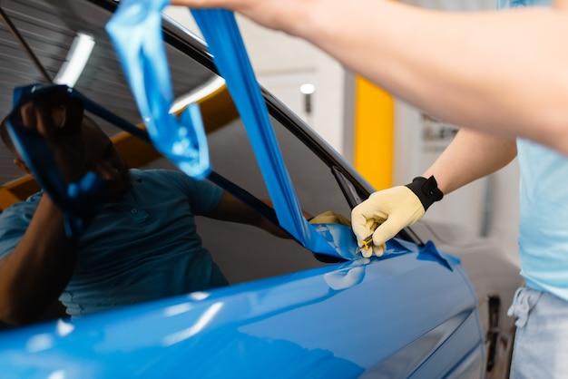 Le mani di un meccanico maschio installano una pellicola o un foglio di vinile protettivo sulla portiera del veicolo. il lavoratore fa i dettagli automatici. protezione della vernice dell'auto, messa a punto professionale