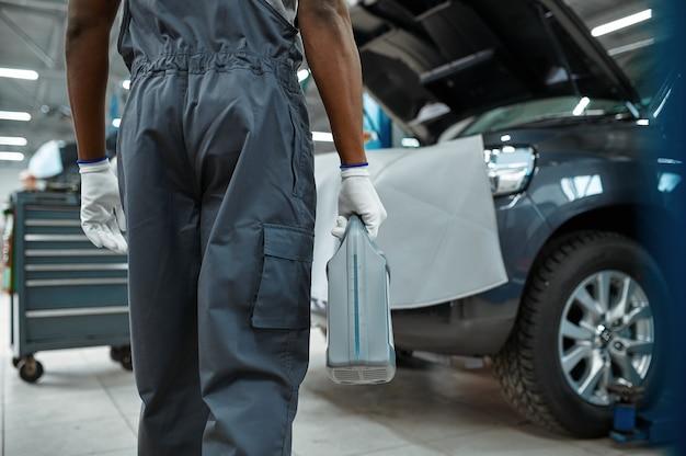 Il meccanico maschio tiene la tanica dell'olio, servizio auto