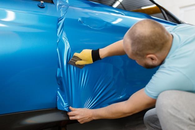 Il meccanico maschio installa un foglio o una pellicola vinilica protettiva sulla portiera del veicolo. il lavoratore fa i dettagli automatici. protezione della vernice dell'auto, messa a punto professionale