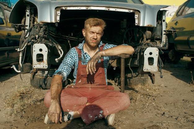 Il meccanico maschio pone sulla discarica di auto. rottami di automobili, cianfrusaglie di veicoli, rifiuti di automobili. trasporti abbandonati, danneggiati e frantumati, cantiere di demolizione