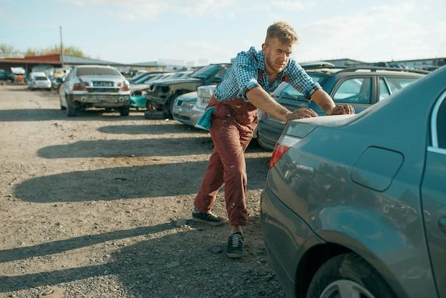 Meccanico maschio che spinge l'auto sulla discarica. rottami di automobili, cianfrusaglie di veicoli, rifiuti di automobili. trasporti abbandonati, danneggiati e frantumati, cantiere di demolizione