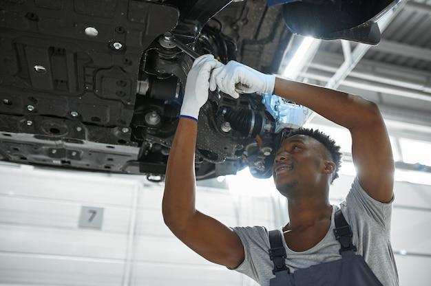 Il meccanico maschio ripara le sospensioni dell'auto, il servizio auto