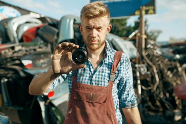 Il meccanico maschio mostra la macchina dell'ingranaggio sulla discarica. rottami di automobili, cianfrusaglie di veicoli, rifiuti di automobili. trasporti abbandonati, danneggiati e frantumati, cantiere di demolizione