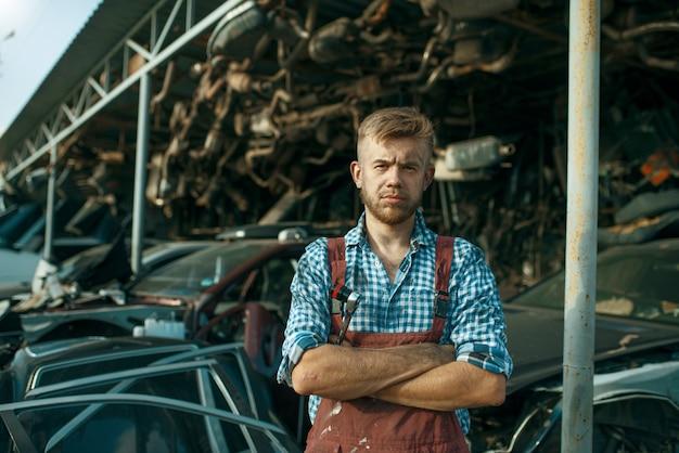 Meccanico maschio alla pila di auto sulla discarica. rottami di automobili, cianfrusaglie di veicoli, rifiuti di automobili. trasporti abbandonati, danneggiati e frantumati, cantiere di demolizione